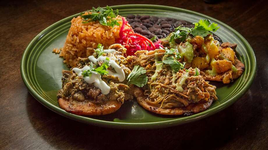 "The huaraches ($14) are three thick tortilla ""sandals"" with three kinds of pork: chile verde, carnitas and al pastor with pineapple, plus black beans and rice. Photo: John Storey, Special To The Chronicle"
