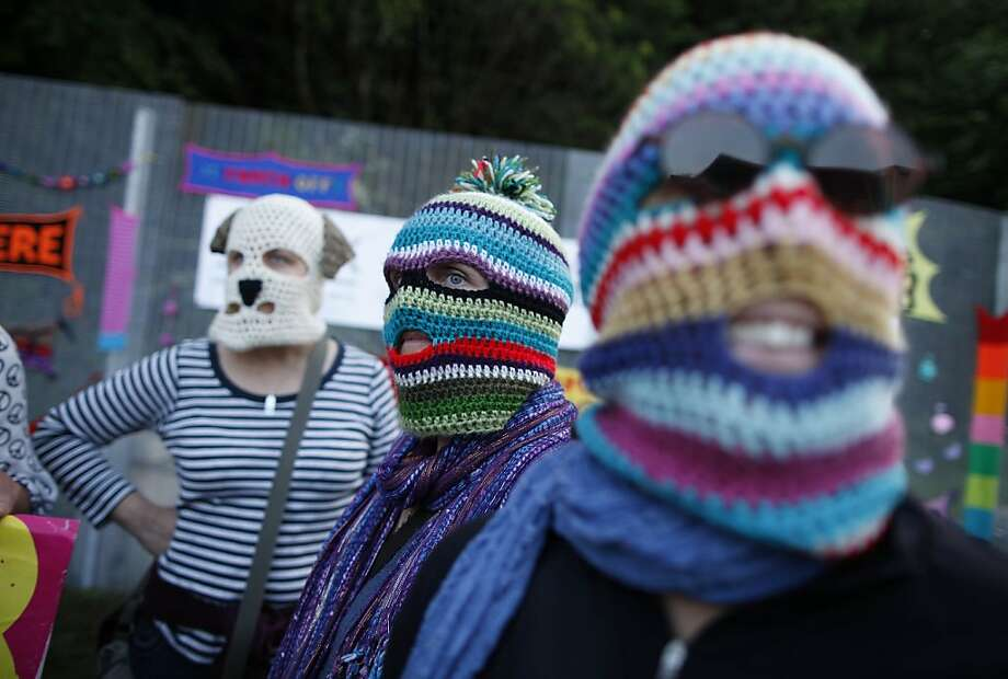 Down with hypothermia!Protesters wearing knit balaclavas protest at the fence near the G-8 
