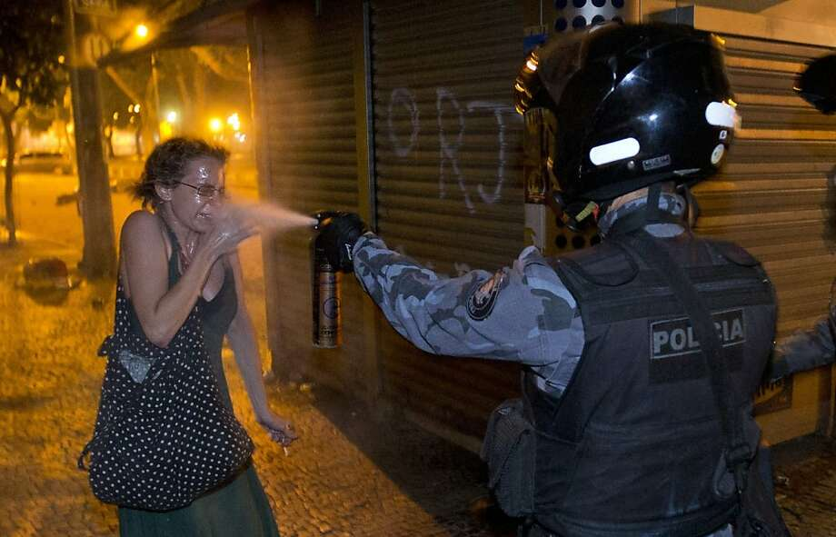 Doused at point-blank range: A military policeman fires pepper spray into the face of a protester during a demonstration in Rio de Janeiro. Demonstrators massed in at least seven Brazilian 