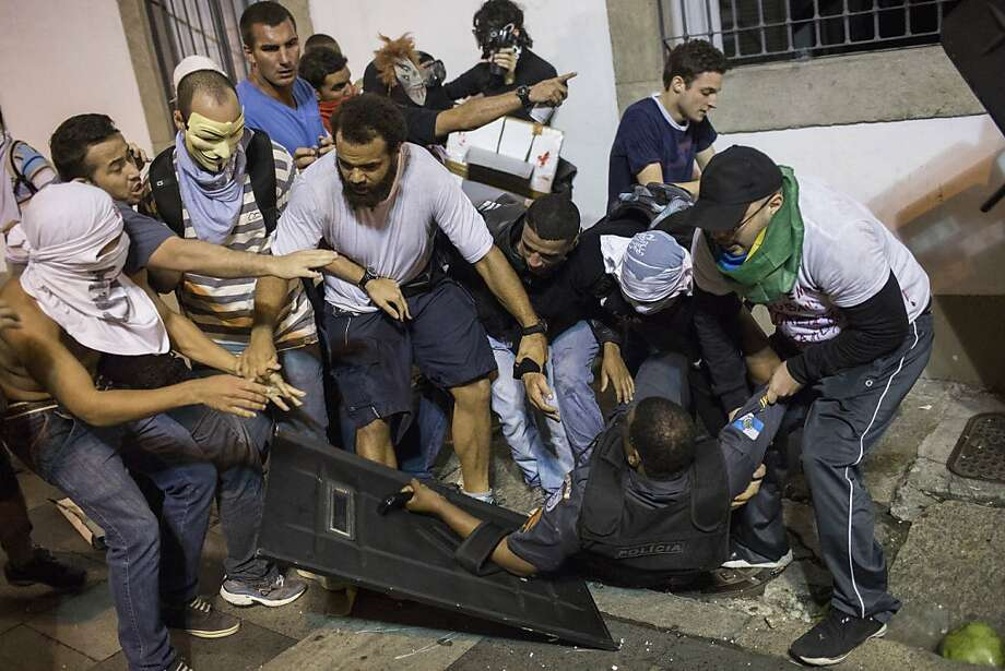Aiding their opponent: Some demonstrators try to help a police officer who was injured in a clash with 