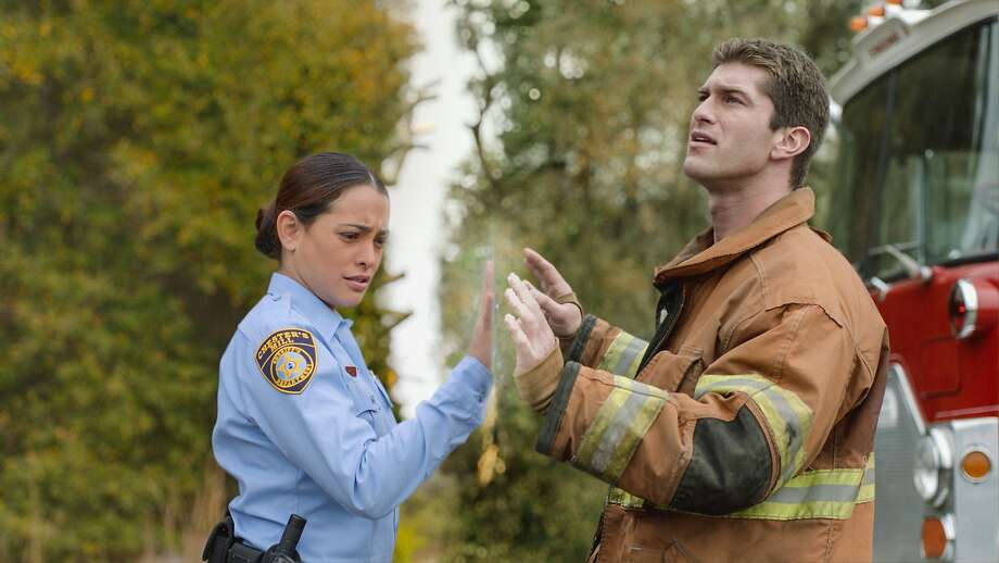 Under the Dome television series: Deputy Linda (Natalie Martinez, left) and her fiancee Rusty (Josh Carter), find themselves separated by a massive transparent dome that has suddenly fallen on the town of Chester's Mil in the first season of the series. UNDER THE DOME is based on Stephen King's Best-selling novel. CBS Broadcasting Inc. All Rights Reserved. Photo: Best Possible Screen Grab, CBS