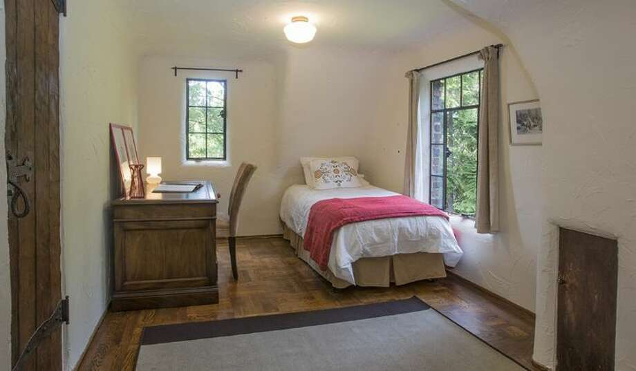 Bedroom of 2635 N.W. 92nd St. The 2,360-square-foot brick Tudor, built in 1931, has four bedrooms, 1.75 bathrooms, coved and vaulted ceilings, plaster walls, iron detailing, a rec room, a balcony and two fireplaces on one-third of an acre. It's listed for $773,000, although a sale is pending. Photo: Courtesy Gloria Jackson, Windermere Real Estate