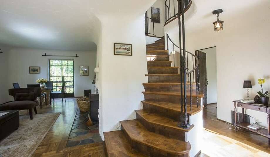 Stairs of 2635 N.W. 92nd St. The 2,360-square-foot brick Tudor, built in 1931, has four bedrooms, 1.75 bathrooms, coved and vaulted ceilings, plaster walls, iron detailing, a rec room, a balcony and two fireplaces on one-third of an acre. It's listed for $773,000, although a sale is pending. Photo: Courtesy Gloria Jackson, Windermere Real Estate