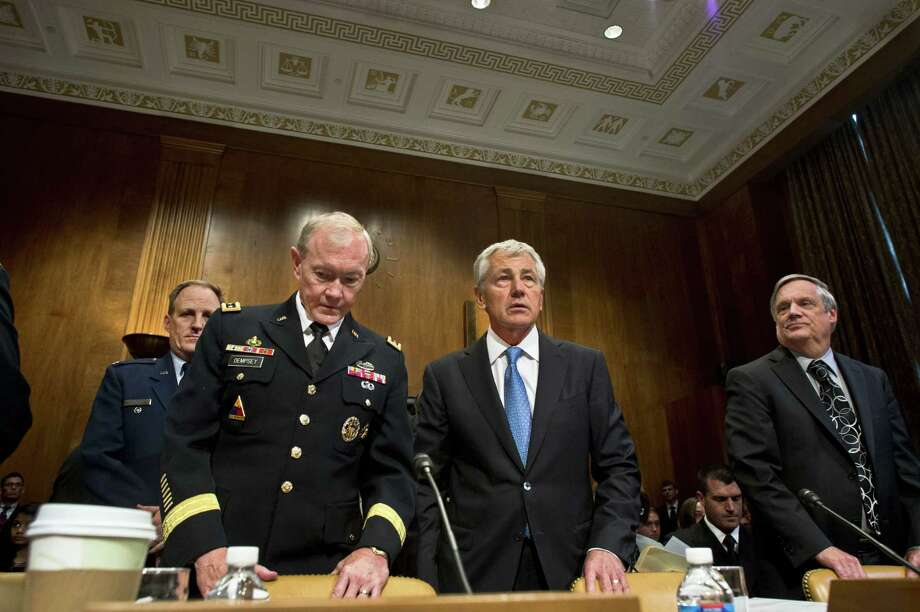 Secretary of Defense Chuck Hagel, center, Chairman of the Joint Chiefs of Staff Gen. Martin E. Dempsey, left and Under Secretary of Defense (Comptroller) and Chief Financial Officer Robert F. Hale, right, take their seats to begin testimony before the Senate Budget Committee June 12. Photo: DOD