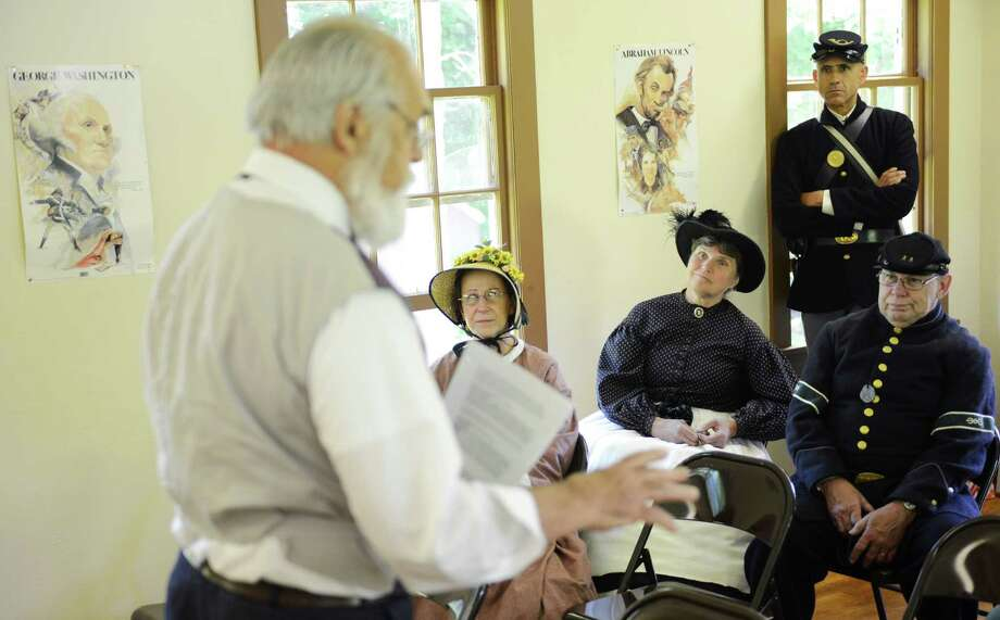 Re-enactors listen to Ernie Barker, of Bantam, Conn., speak during the Living History Civil War re-enactment at the Little Red School House in New Fairfield, Conn. on Saturday, June 15, 2013.  Barker portrayed Frederick Lewis, an 1880s Connecticut statesman and Civil War veteran who is reflecting on his years fighting for the Union through letters to loved ones. Photo: Tyler Sizemore / The News-Times