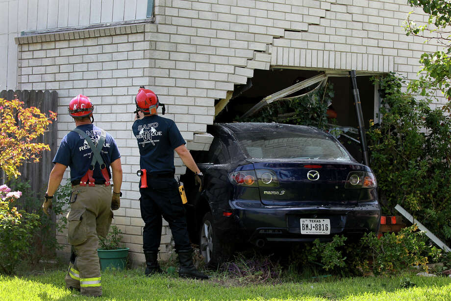 "San Antonio firefighters inspect a home located at 15,530 Spring Summit after a four-door Mazda crashed into it Tuesday June 18, 2013. The car's driver, John Rodiguez, allegedly fell asleep while driving the vehicle and was not seiously injured. Homeowner Carlos Zapata,62, was at work at the time of the accident and after arriving at the scene said, ""nobody got hurt, thank God for that."" Photo: JOHN DAVENPORT, SAN ANTONIO EXPRESS-NEWS / ©San Antonio Express-News"