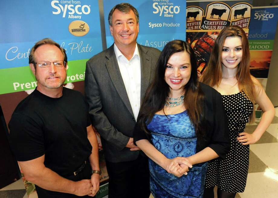 "Laura Laz, CEO and founder of ChefKey, second from right, joins culinary liaison David Britton, left, Dennis Bailey, Sysco director of marketing, second from left, and Nicole Emmons, 18, of Hey! Cupcake Girl, right, on Tuesday, June 18, 2013, at Sysco headquarters in Halfmoon, N.Y. ChefKey is a locally based social-media site that is aiming to be ""Facebook for foodies."" (Cindy Schultz / Times Union) Photo: Cindy Schultz / 10022860A"