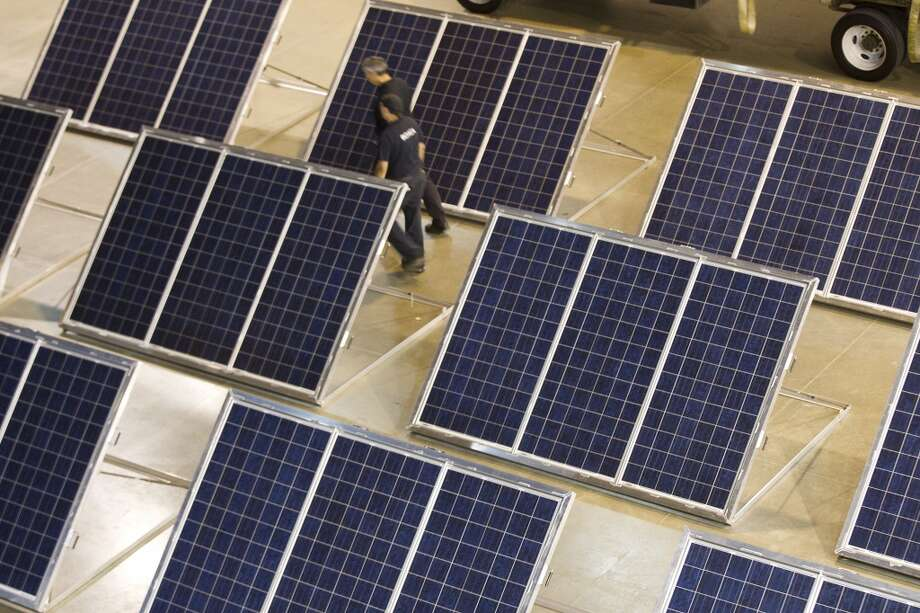 A pair of workers walk past an array of solar panels during a tour and demonstration of a solar-diesel powered disaster relief vehicle and 26-foot trailer at Reliant Center Tuesday, June 18, 2013, in Houston. The vehicle is designed to deliver immediate power, emergency shelter, access to news and information and Wi-Fi internet connectivity to those in need. Photo: Brett Coomer, Houston Chronicle