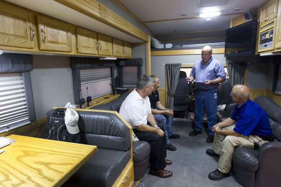 NRG Energy workers talk inside solar-diesel powered disaster relief vehicle and 26-foot trailer at Reliant Center Tuesday, June 18, 2013, in Houston. The vehicle is designed to deliver immediate power, emergency shelter, access to news and information and Wi-Fi internet connectivity to those in need. Photo: Brett Coomer, Houston Chronicle