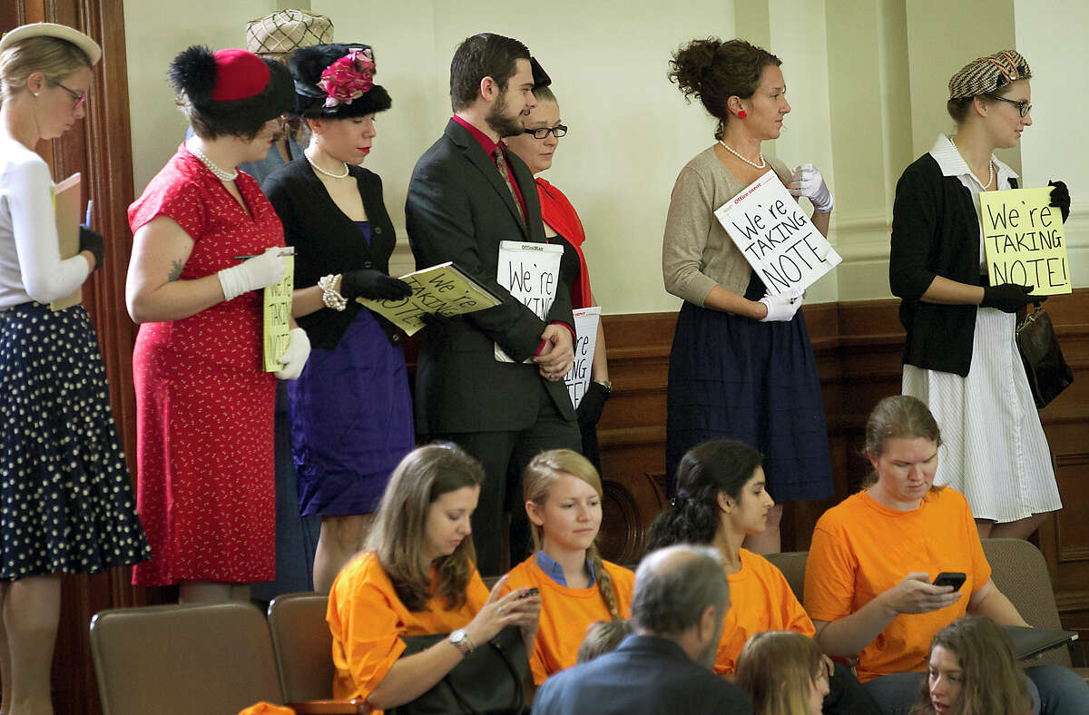 Women's rights supporters dressed in period costumes and others donned orange t-shirts to express their opposition to four abortion-related bills being addressed in the Texas Senate Tuesday afternoon June 18, 2013 as part of Governor Perry's additional items for the called special session. Republican sponsors say the bills are intended to protect women's health and protect fetuses from pain. Abortion providers say that's a convenient fiction, that the bills are intended to make providing abortions so difficult that -- while the procedure remains legal -- there will be almost no legal way to get an abortion in Texas because most of the clinics will be force to close. RALPH BARRERA / AMERICAN-STATESMAN