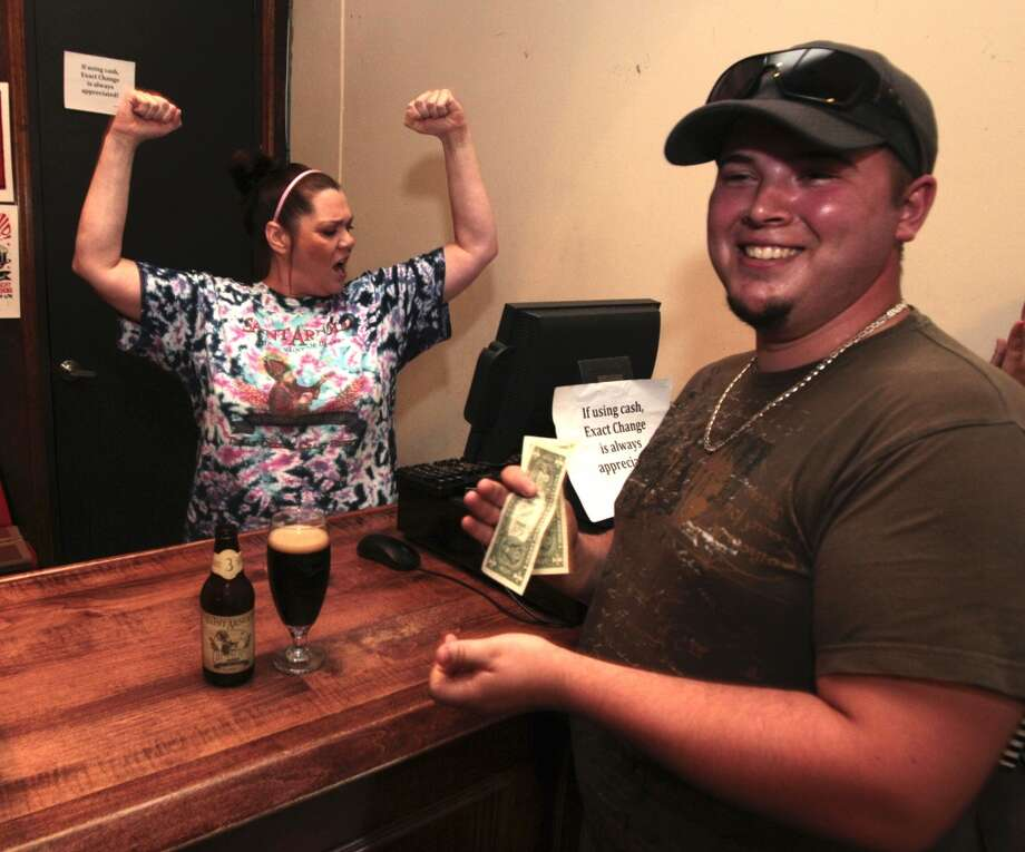 Janet Hamric celebrates after ringing up the first Saint Arnold beer sold on site, directly to a customer. Dale Edwards was having lunch at the brewery Tuesday when it was announced Bishop's Barrel No. 3 would be sold during the afternoon tour.