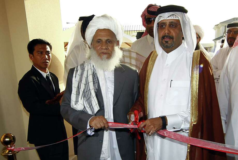 Qatari Assistant Minister for Foreign Affairs Ali bin Fahd al-Hajri (right) and Taliban official Jan Mohammad Madani cut the ribbon at the opening ceremony of the Taliban office in Doha, Qatar. The office will be used for peace talks and to explain Taliban views to other countries. Photo: Osama Faisal / Associated Press