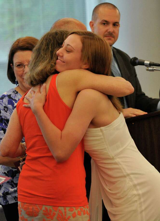 Catherine Cote, right, hugs guidance counselor Marian Bauer while accepting her certificate during the Alternative Routes to Success Program, Home Instruction Department and Out-of-District Program recognition ceremony at the Government Center in Stamford on Tuesday, June 18, 2013. Photo: Jason Rearick / Stamford Advocate