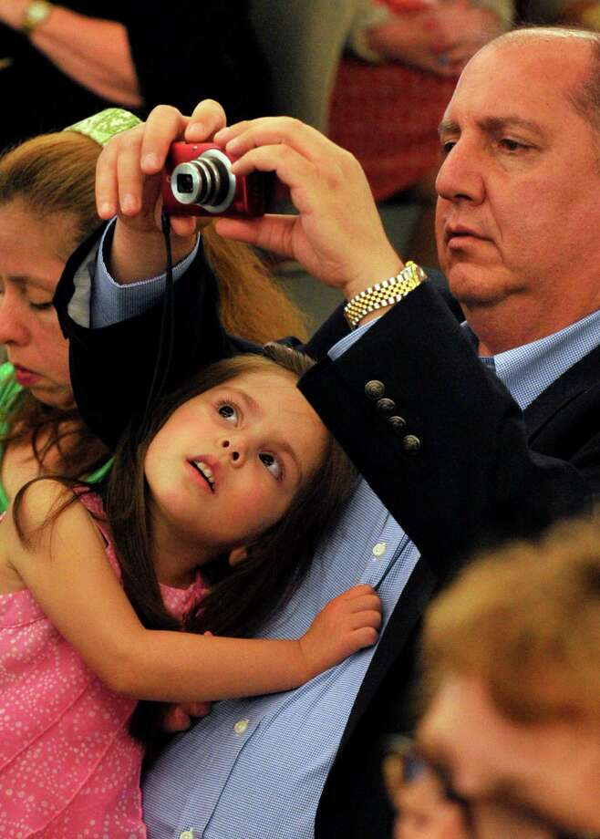 David Ballin and his four-year-old daughter, Natalie, focus on David's niece, Faith Ballin, during the Alternative Routes to Success Program, Home Instruction Department and Out-of-District Program recognition ceremony at the Government Center in Stamford on Tuesday, June 18, 2013. Photo: Jason Rearick / Stamford Advocate