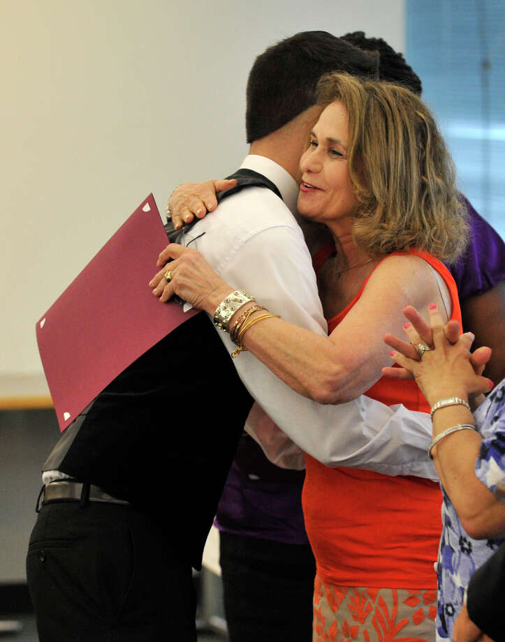 Sebastian Perez hugs guidance counselor Marian Bauer during the Alternative Routes to Success Program, Home Instruction Department and Out-of-District Program recognition ceremony at the Government Center in Stamford on Tuesday, June 18, 2013. Photo: Jason Rearick / Stamford Advocate