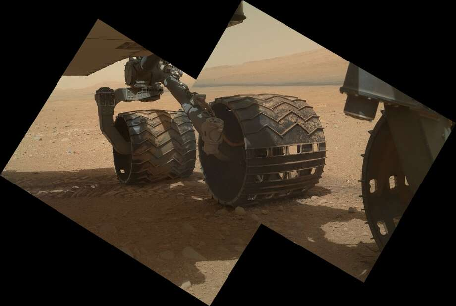 This image provided by NASA shows the Curiosity rover's three left wheels. Since landing on Mars on Aug. 5, 2012, Curiosity has driven more than the length of a football field. It will resume driving this week after it completes its health checkups. (AP Photo/NASA)