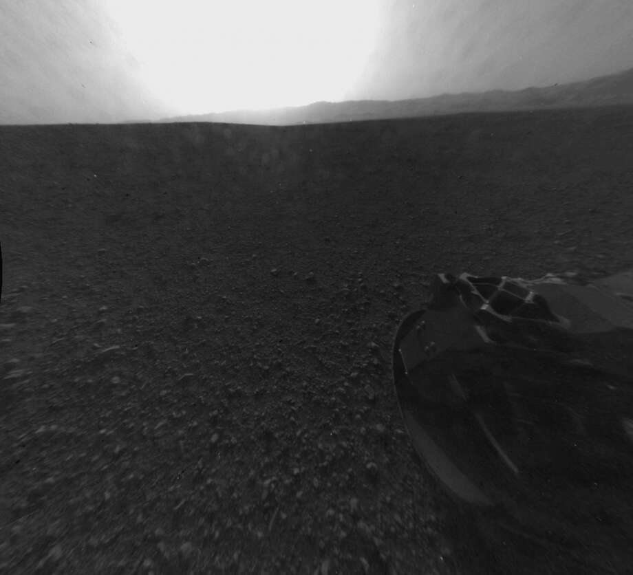 "This photo provided by NASA shows a full-resolution version of one of the first images taken by a rear Hazard-Avoidance camera on NASA's Curiosity rover, which landed on Mars the Sunday evening, Aug. 5, 2012. The image was originally taken through a ""fisheye"" wide-angle lens, but has been ""linearized"" so that the horizon looks flat rather than curved. A Hazard-avoidance camera on the rear-left side of Curiosity obtained this image. Part of the rim of Gale Crater, which is a feature the size of Connecticut and Rhode Island combined, stretches from the top middle to the top right of the image. One of the rover's wheels can be seen at bottom right. (AP Photo/NASA/JPL-Caltech)"