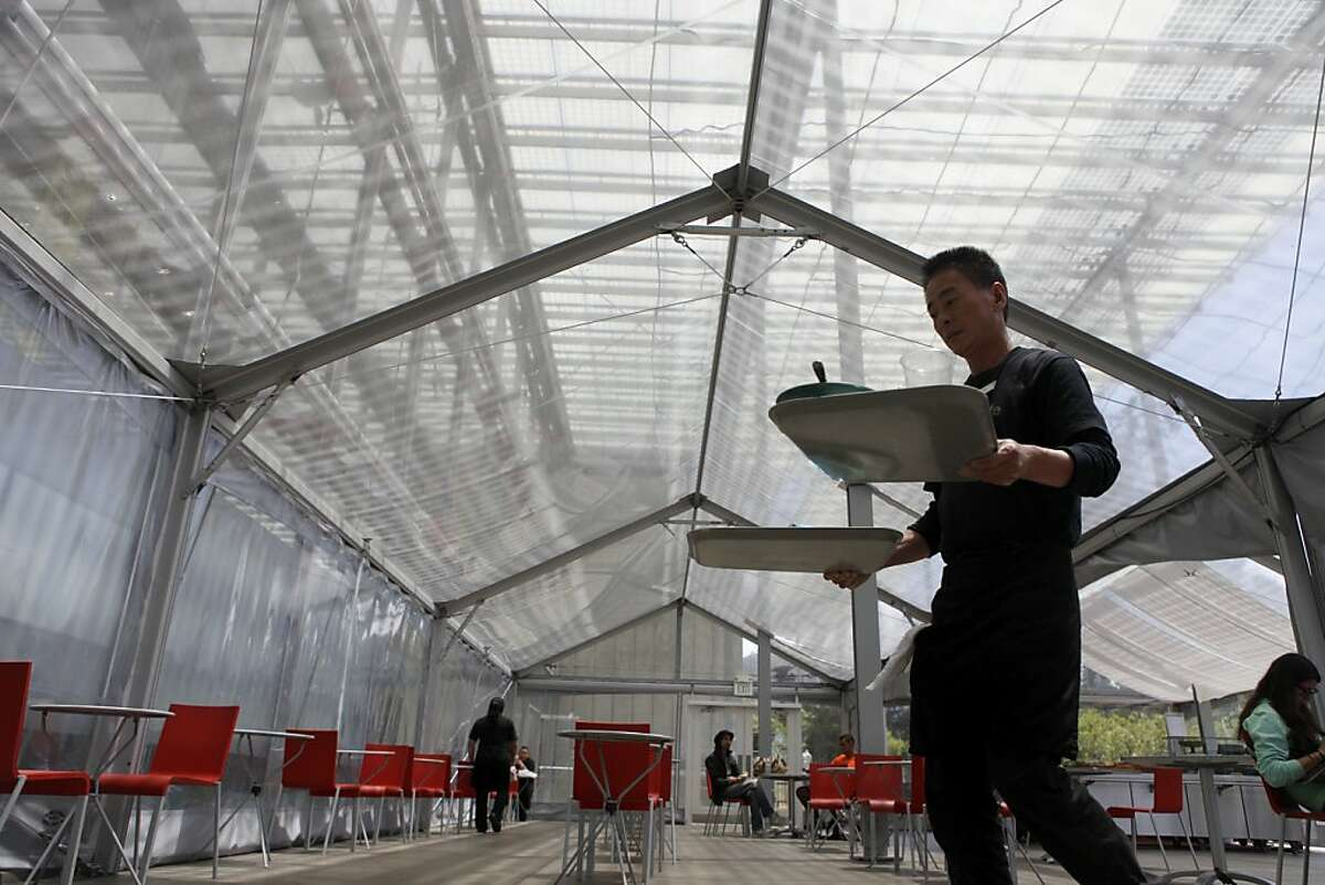 An employee at the California Academy of Sciences clears tables in the tent which is temporarily being used as a cafe while the planning for the new dining pavilion is in the works.