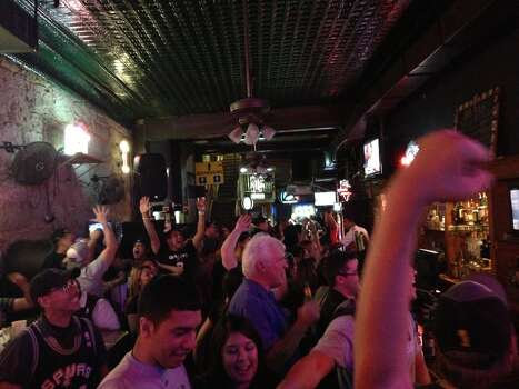 Spurs fans celebrate a Kawhi Leonard dunk over the Heat's Mike Miller in the middle of the first quarter at Leapin' Lizard downtown. Photo: Benjamin Olivo / MySA.com