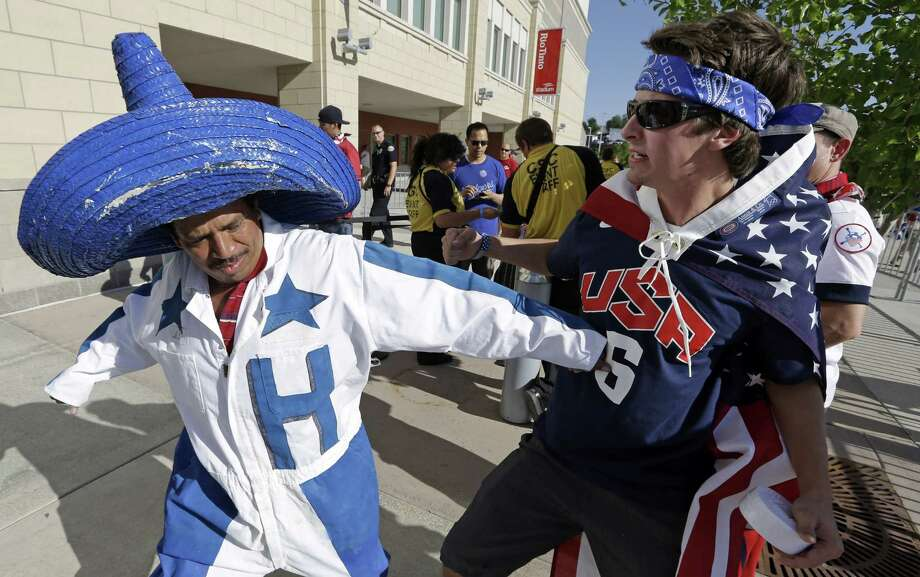 U.S. soccer fan Kyle Flowers, right, and Honduras fan Harly Redondo, left, exchange blows as the play before the start an World Cup qualifying soccer match between Honduras and the U.S. at Rio Tinto Stadium on Tuesday, June 18, 2013, in Sandy, Utah.  (AP Photo/Rick Bowmer) Photo: Rick Bowmer, Associated Press / AP