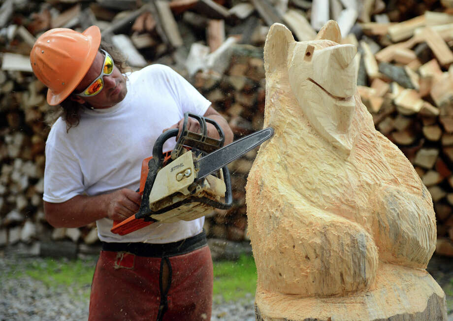 Jay Dubac works on one of his bear statue projects at his home in Monroe, Conn. on Tuesday June 18, 2013. Dubac wants to sell his creations and firewood at the Monroe Farmer's Market but they have so far refused letting him set up a spot there. He has been told his works are crafts and not farm product and that his firewood has to be certified by the state first. Photo: Christian Abraham / Connecticut Post
