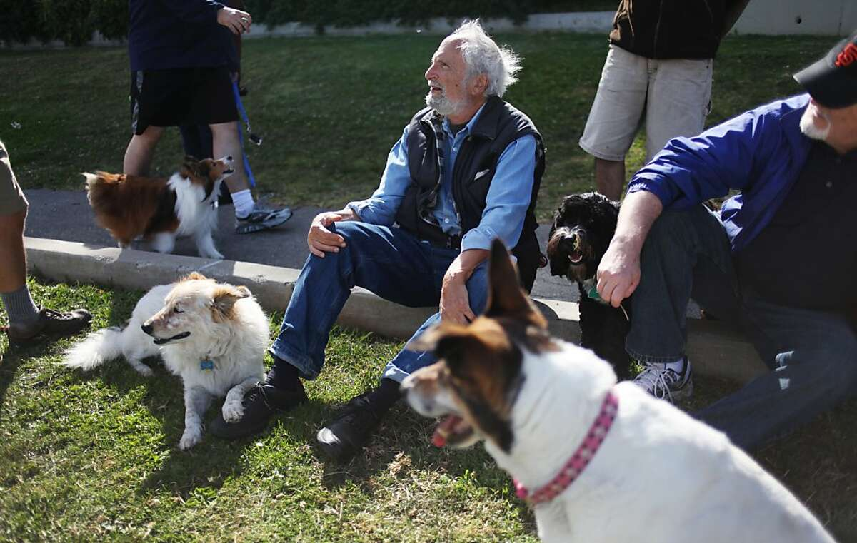 """Mike Pincus talks with other dog owners in Holly Park on June 18, 2013 in San Francisco, Calif. His dog Omar, named after the character in """"The Wire,"""" is the black dog to the right of him. At right is Bill Carr and his three-legged dog Charlotte (foreground)."""