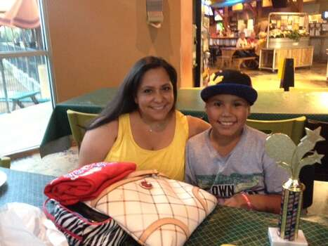 "Under the glow of a flat screen TV at MoMak's Backyard Malts & Burgers, the Braves little-league team was having a year-end party; two young Heat fans were among them, watching the first quarter with their parents. ""He doesn't know any better,"" said Elisa Ryan, mother of 9-year-old Devin Ryan, a self-proclaimed Heat fan.  Devin is shy, but when the prospect of the Spurs winning the Finals comes up he is adamant. ""He's gonna wear a Spurs shirt!"" his mother says, and Devin shakes his head ""no"" before she can finish the sentence. Photo: Sarah L. Tressler / San Antonio Express-News"