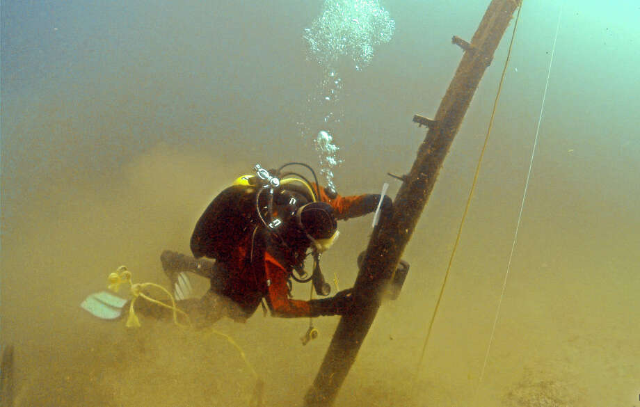 Jim Nowka inspects a wooden beam extending from the floor of Lake Michigan that experts believe might be from the Griffin, a ship that was used by French explorers in 1679. Photo: Great Lakes Exploration Group / Associated Press