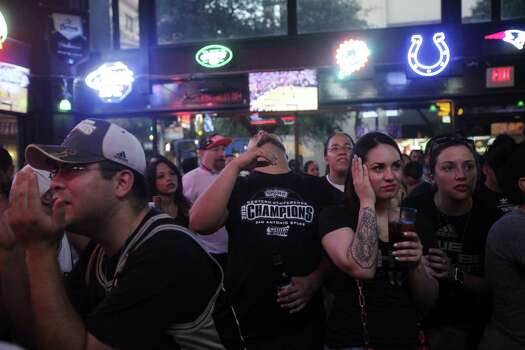 Left to right: Erik Estrada, Luis Lara, and Sabrina Chavez, all of San Antonio, watch the NBA Finals at Ticket Sports Pub on Tuesday, June 18, 2013. Photo: Abbey Oldham, San Antonio Express-News / © San Antonio Express-News