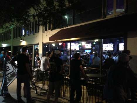 Spurs fans at The Ticket sports bar at Losoya and Houston streets take in Game 6, including about 30 fans out on the street. Photo: Benjamin Olivo / MySA.com