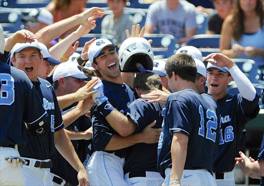 North Carolina players embrace Brian Holberton, center right with back to camera, after he hit a two-run home run against LSU in the first inning of an NCAA College World Series elimination baseball game in Omaha, Neb., Tuesday, June 18, 2013. (AP Photo/Eric Francis) Photo: Eric Francis