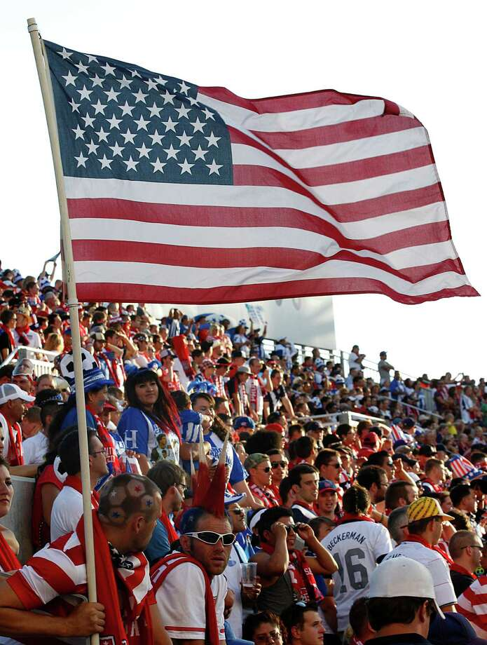 SANDY, UT - JUNE 18: Fans of the United States cheer and fly an American flag during a game against Honduras during the first half of a World Cup qualifying match on June 18, 2013 at Rio Tinto Stadium in Sandy, Utah. Photo: George Frey, Getty Images / 2013 Getty Images