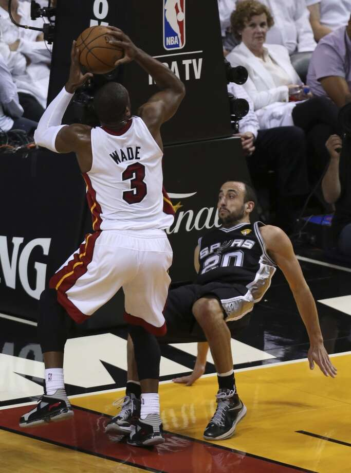 San Antonio Spurs' Manu Ginobili falls down while defending Miami Heat's Dwyane Wade during the first half of Game 6 of the NBA Finals at American Airlines Arena on Tuesday, June 18, 2013 in Miami. (Jerry Lara/San Antonio Express-News)