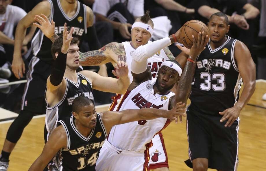 Miami Heat's LeBron James looks to dish to a teammate while under pressure from San Antonio Spurs' Gary Neal and Tiago Splitter during the first half of Game 6 of the NBA Finals at American Airlines Arena on Tuesday, June 18, 2013 in Miami. (Jerry Lara/San Antonio Express-News)