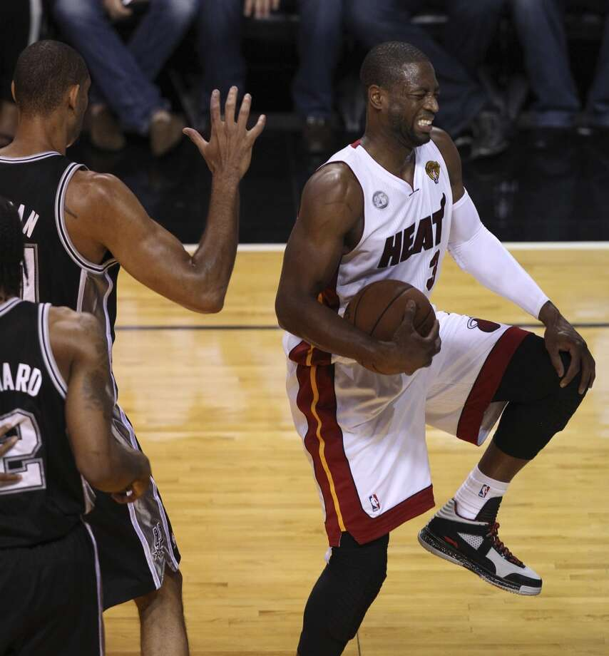 Miami Heat's Dwyane Wade holds his knee as he lands with the ball while under pressure from San Antonio Spurs' Tim Duncan during the first half of Game 6 of the NBA Finals at American Airlines Arena on Tuesday, June 18, 2013 in Miami. (Kin Man Hui/San Antonio Express-News)