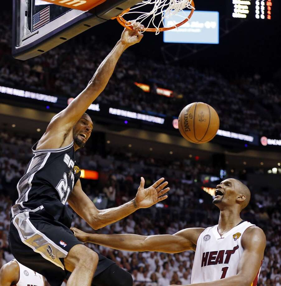 San Antonio Spurs' Tim Duncan hangs on the rim after dunking over Miami Heat's Chris Bosh during first half action in Game 6 of the 2013 NBA Finals Tuesday, June 18, 2013 at American Airlines Arena in Miami. (Edward A. Ornelas/San Antonio Express-News)