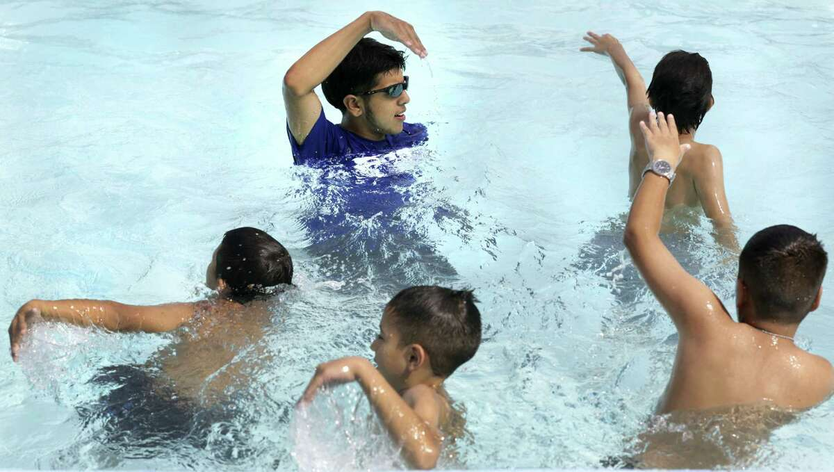 Damien Guzman, a lifeguard for the city, demonstrates a basic swimming stroke to a group of boys at Woodlawn Pool during the World's Largest Swimming Lesson.