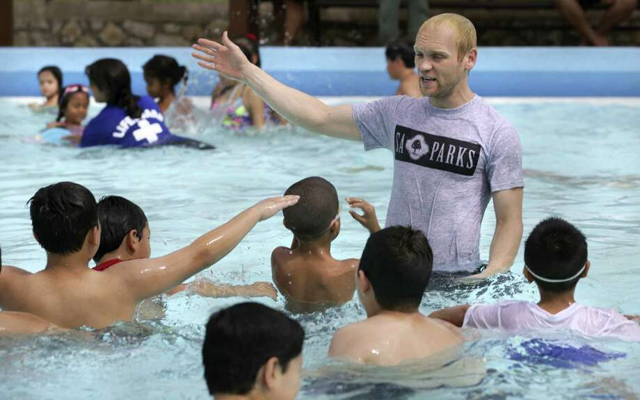 Rusty Ives, a lifeguard and swim coach for the city, shows a group of boys the basics of swimming. The main sponsors of Tuesday's event were the National Recreation and Park Association, American Red Cross and Learn to Swim Foundation. Photo: Bob Owen / San Antonio Express-News