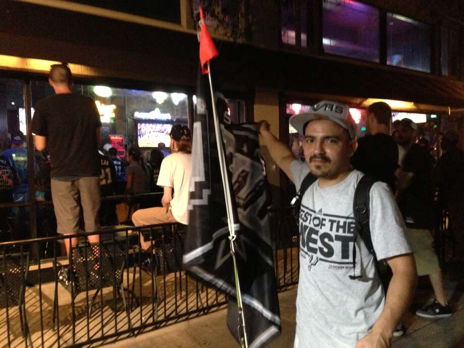 "Victor Leal was riding around downtown on his bike with a large Spurs flag mounted on the back. ""I just felt like I needed to show my Spurs spirit,"" Leal said, hanging outside The Ticket sports bar on Losoya and Houston streets. ""The Spurs, they are legendary at closing out games. The Spurs, they don't leave teams lingering. We're gonna do it tonight."" Photo: Benjamin Olivo / MySA.com"