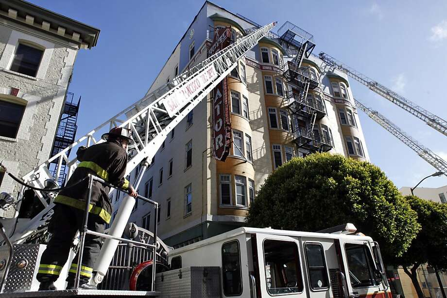 Firefighters mop up as residents of the Senator Hotel stood out on the street after a fire broke out on the roof of the building on Tuesday, June 18, 2013, in San Francisco, Calif. Photo: Carlos Avila Gonzalez, The Chronicle