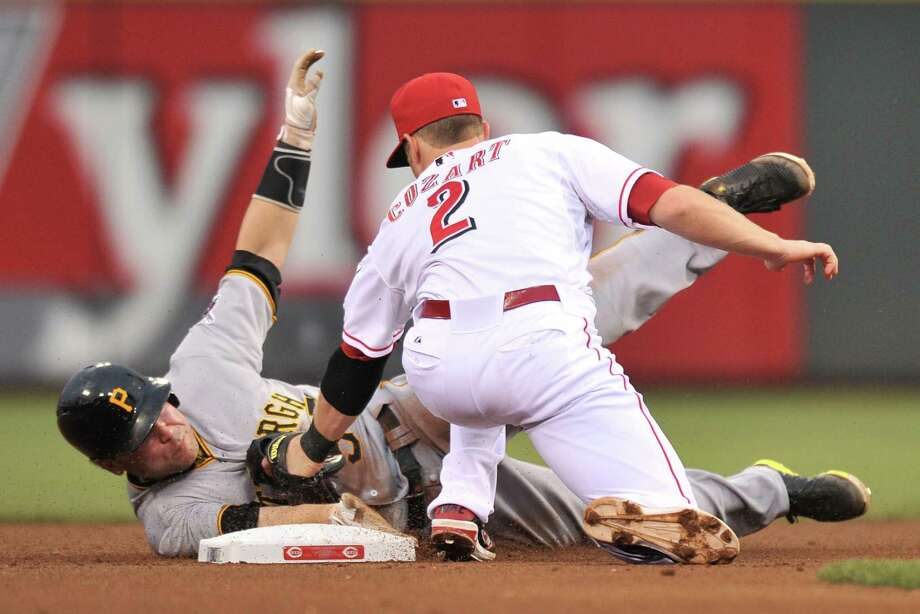 The Pirates' Russell Martin steals second base, barely beating the tag of the Reds' Zack Cozart. Photo: Jamie Sabau / Getty Images