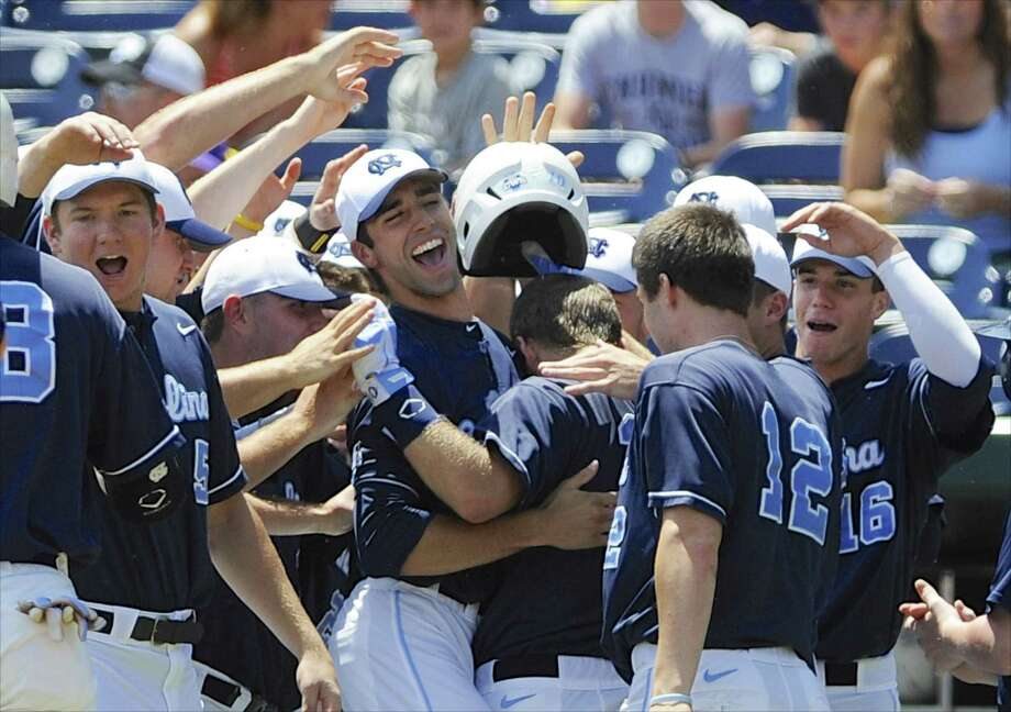 North Carolina players rejoice after Brian Holberton (center, back to camera) hit a two-run homer in the first inning of a 4-2 win over LSU in Omaha, Neb. Photo: Eric Francis / Associated Press