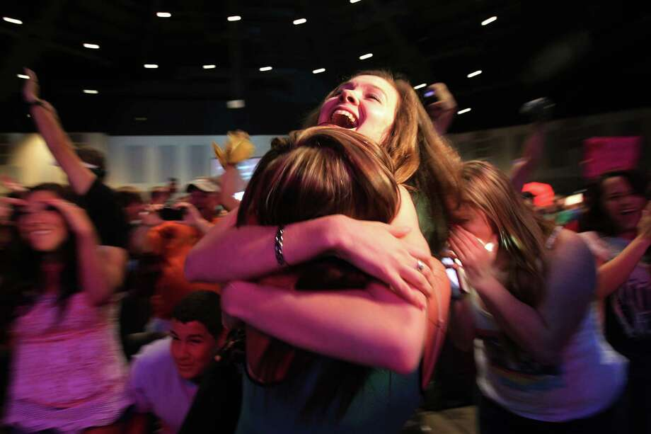 "Monica Bradbery, 22, embraces friend Brooke Stanfield on Tuesday night after her sister Danielle is announced the winner of ""The Voice"" during a watch party at the Community of Faith in Hockley. Photo: Mayra Beltran, Staff / © 2013 Houston Chronicle"
