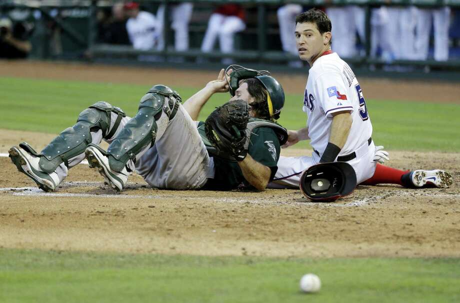 Texas' Ian Kinsler looks back to see the ball after colliding with Oakland catcher John Jaso while scoring in the third. Photo: Tony Gutierrez / Associated Press