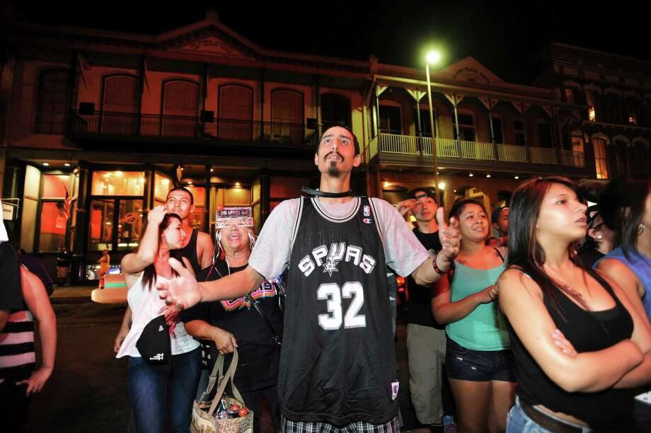 Steven Thompson and other fans in downtown San Antonio react as the Spurs lose to Miami in Game 6 of the NBA Championship series on Tuesday, June 18, 2013. The crowd gathered outside of the Lone Star Cafe and watched through a window. Photo: Billy Calzada, San Antonio Express-News / San Antonio Express-News