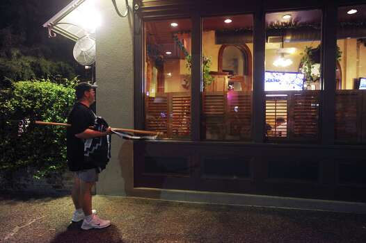 San Antonio Spurs fan Todd Beach watches the game through a window of the Lone Star Cafe in downtown San Antonio as the Spurs go down in defeat to Miami in Game 6 of the NBA Championship Series on Tuesday, June 18, 2013. Photo: Billy Calzada, San Antonio Express-News / San Antonio Express-News