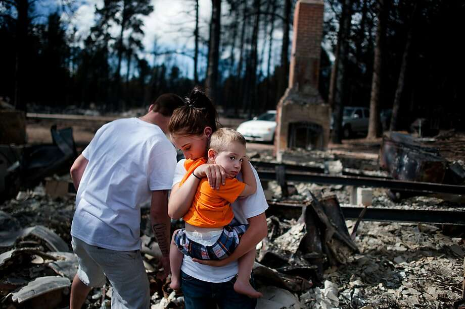 Brandy Burton carries her son Caiyleb Lewis, 2, through the rubble of her family's home  that was completely destroyed in the Black Forest Fire, Tuesday, June 18, 2013, in Colorado Springs, Colo. Residents were allowed back into the area for a short period of time to view the properties that sustained the most damage from the fire. The Black Forest Fire, the most destructive wildfire in Colorado history, has destroyed 502 homes and charred more than 22 square miles. It was 85 percent contained Tuesday. (AP Photo/The Colorado Springs Gazette, Michael Ciaglo)  Photo: Michael Ciaglo, Associated Press