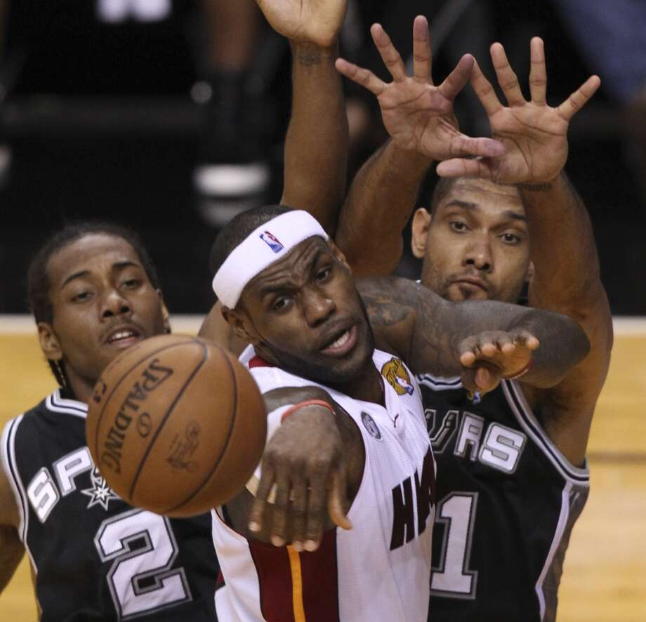 Miami Heat's LeBron James dishes out of the paint while under pressure from San Antonio Spurs' Kawhi Leonard and Tim Duncan during the first half of Game 6 of the NBA Finals at American Airlines Arena on Tuesday, June 18, 2013 in Miami. (Kin Man Hui/San Antonio Express-News)