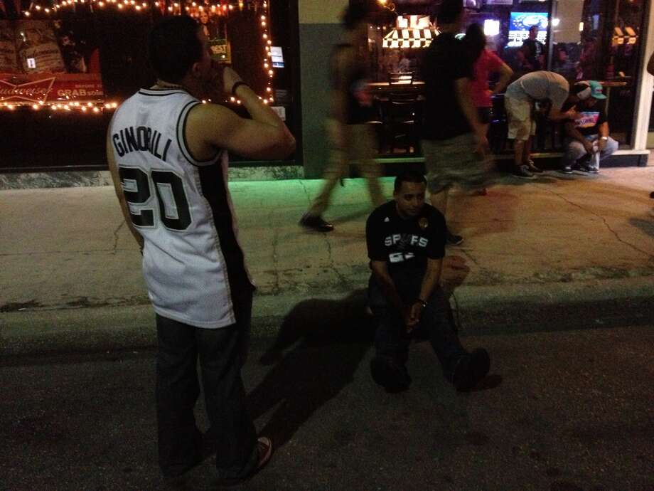 "A depressed Spurs fan sits outside The Ticket on Houston Street, shaking his head in disbelief. A woman walks by chanting ""Thursday Spursday,"" attempting to lift spirits. The once-crowded bar is practically deserted. Photo: Emily Miller / San Antonio Express-News"