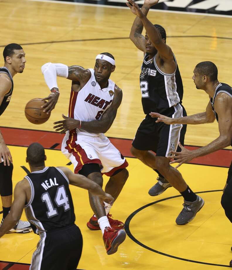 Miami Heat's LeBron James dishes to a teammate while under pressure from San Antonio Spurs' Danny Green, Gary Neal, Kawhi Leonard and Tim Duncan during the second half of Game 6 of the NBA Finals at American Airlines Arena on Tuesday, June 18, 2013 in Miami. (Jerry Lara/San Antonio Express-News)
